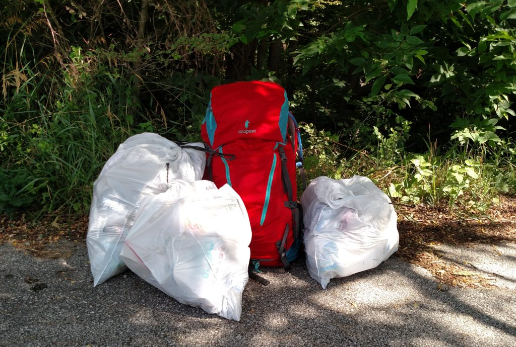Three bags of trash and my cotopaxi backpack on the trail
