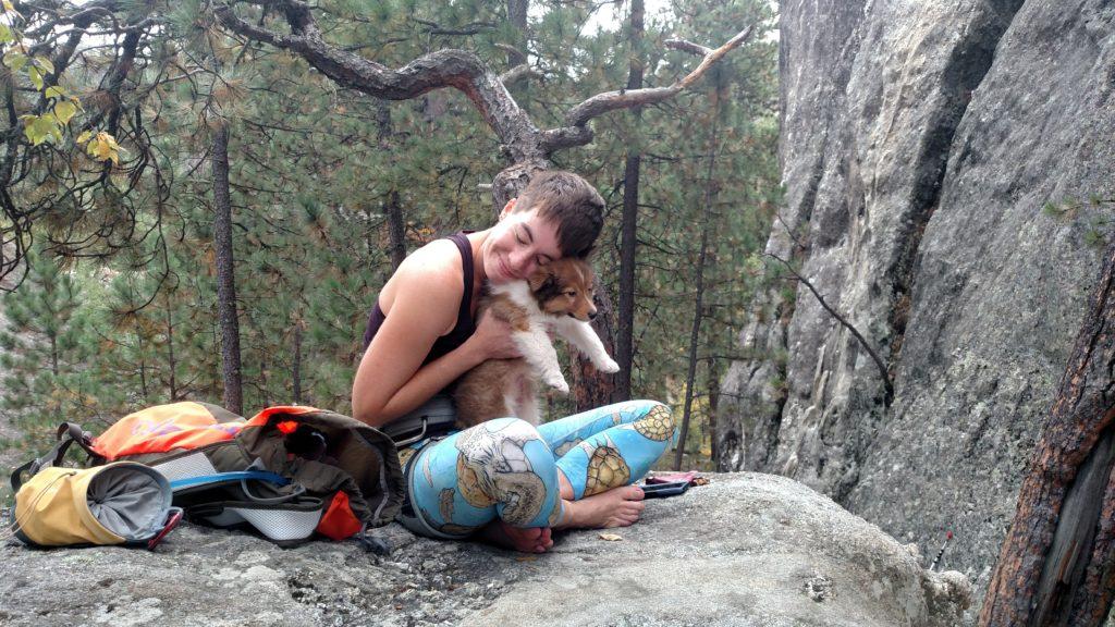 Clarissa sitting on a boulder with Leo.
