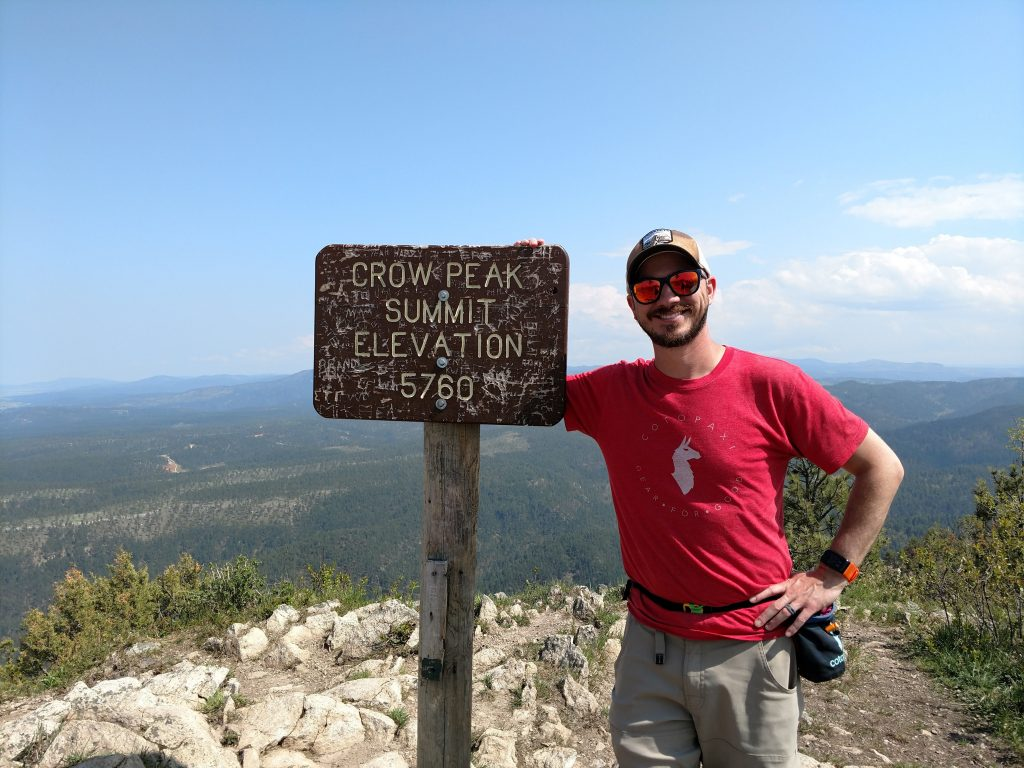 Wade at the summit after successfully hiking Crow Peak