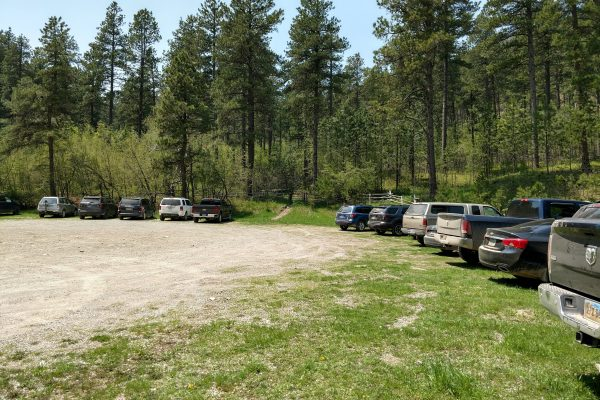 Cars and trucks in the parking area at the trailhead